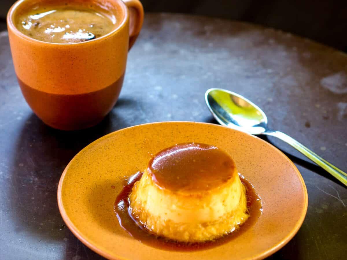 flan de coco casero en un plato delante de una taza de café