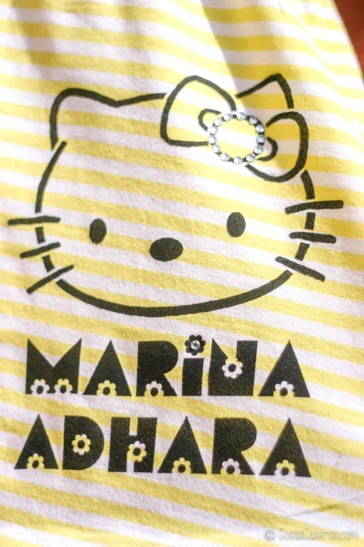 Un vestido de rayas con una imagen de Hello Kitty y el nombre Marina Adhara pintado