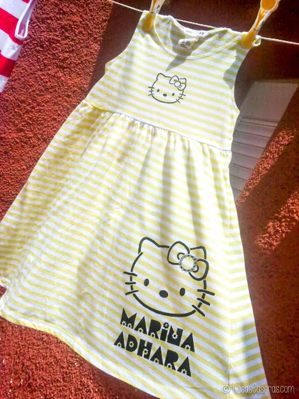 Un vestido de rayas con una imagen de Hello Kitty y el nombre Marina Adhara pintado colgado fuera