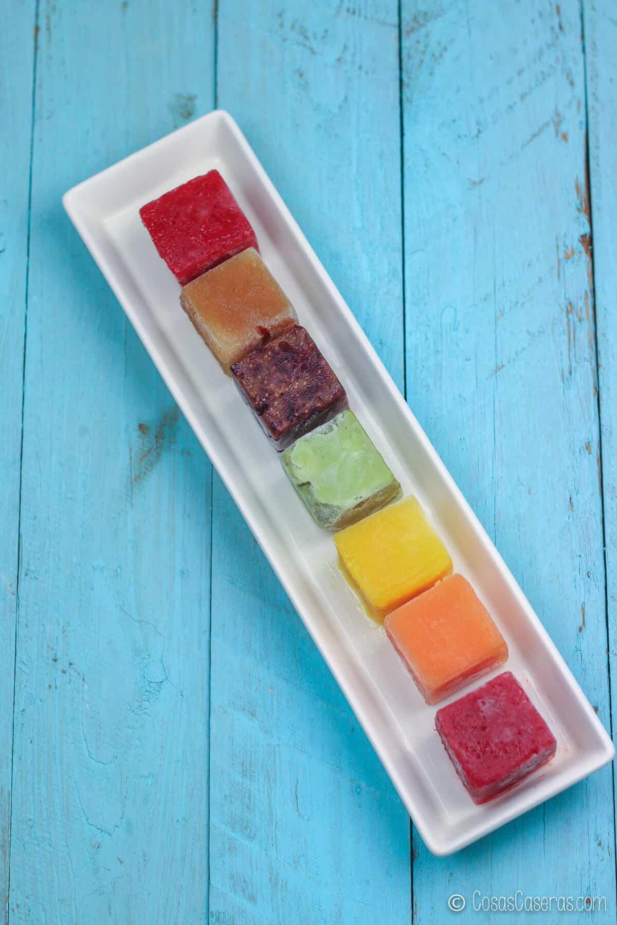 cubitos de fruta de todos colores en un plato blanco