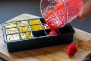 echando puré de fresa a una cubitera