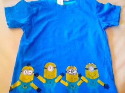 Una camiseta azul con 4 minions pintados en la parte de abajo