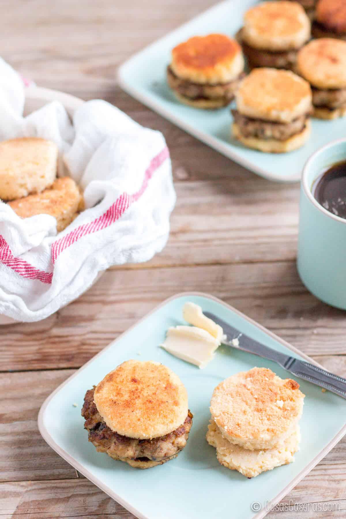 Una salchicha casera dentro de un panecillos de buttermilk al lado de otro panecillo en un plato con un poco de mantequilla. En el fondo hay más salchichas en panecillos.