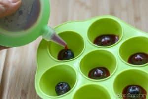 Echando la gelatina roja por encima de los arandanos en las cubiteras