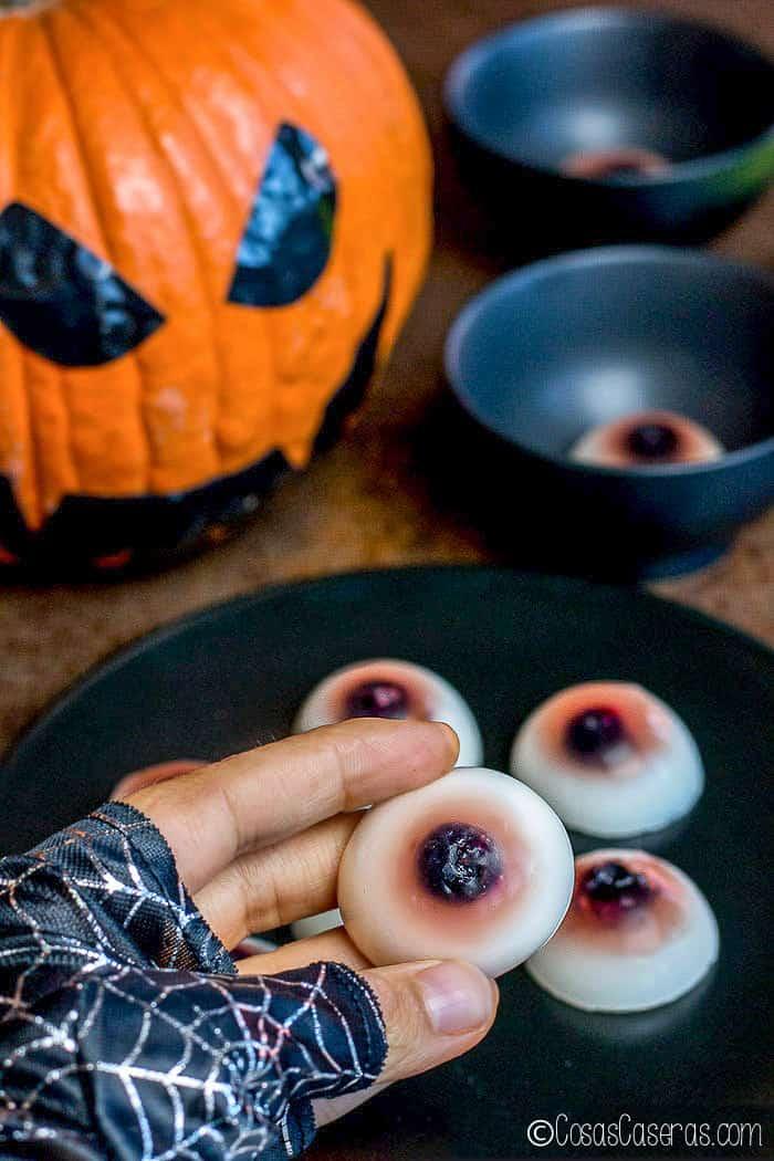 Una mano cogiendo una gominola en forma de ojo de un plato lleno de ellas.