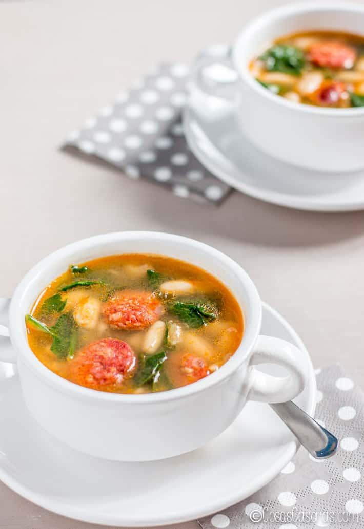 Dos boles de sopa de alubias blancas con chorizo y espinacas
