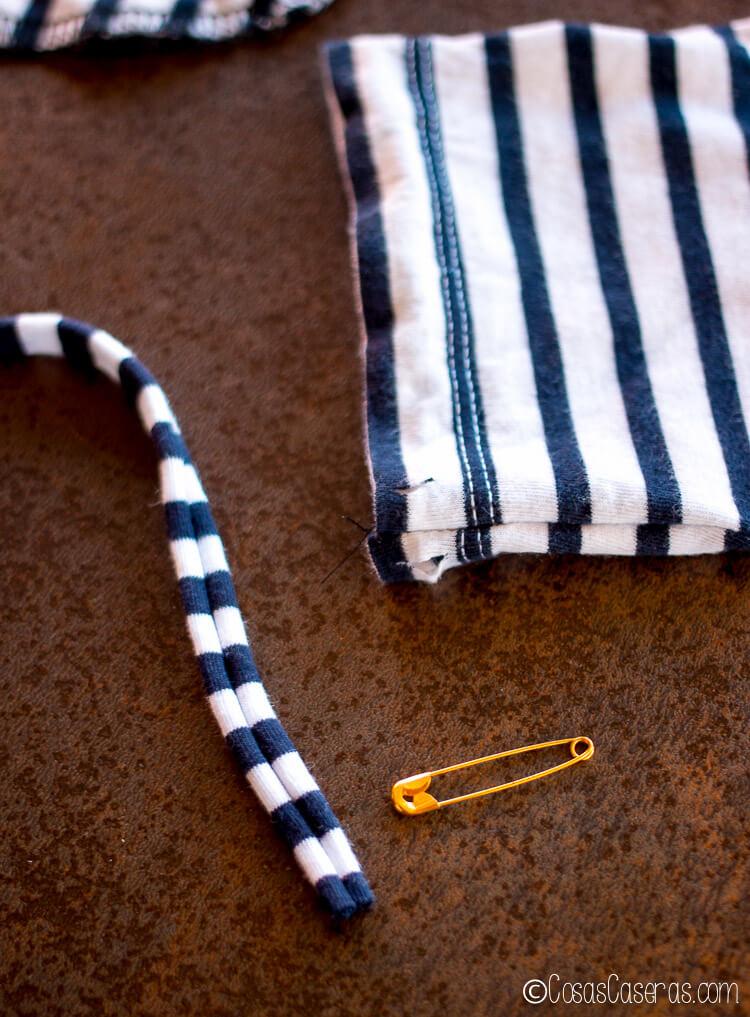 pasando los cordones por el dobladillo.