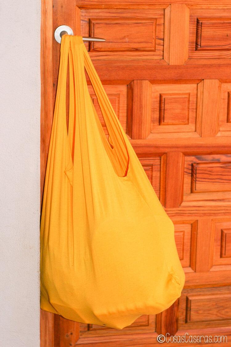 bolsa hecha de una camiseta amarilla, llena y colgada de una puerta