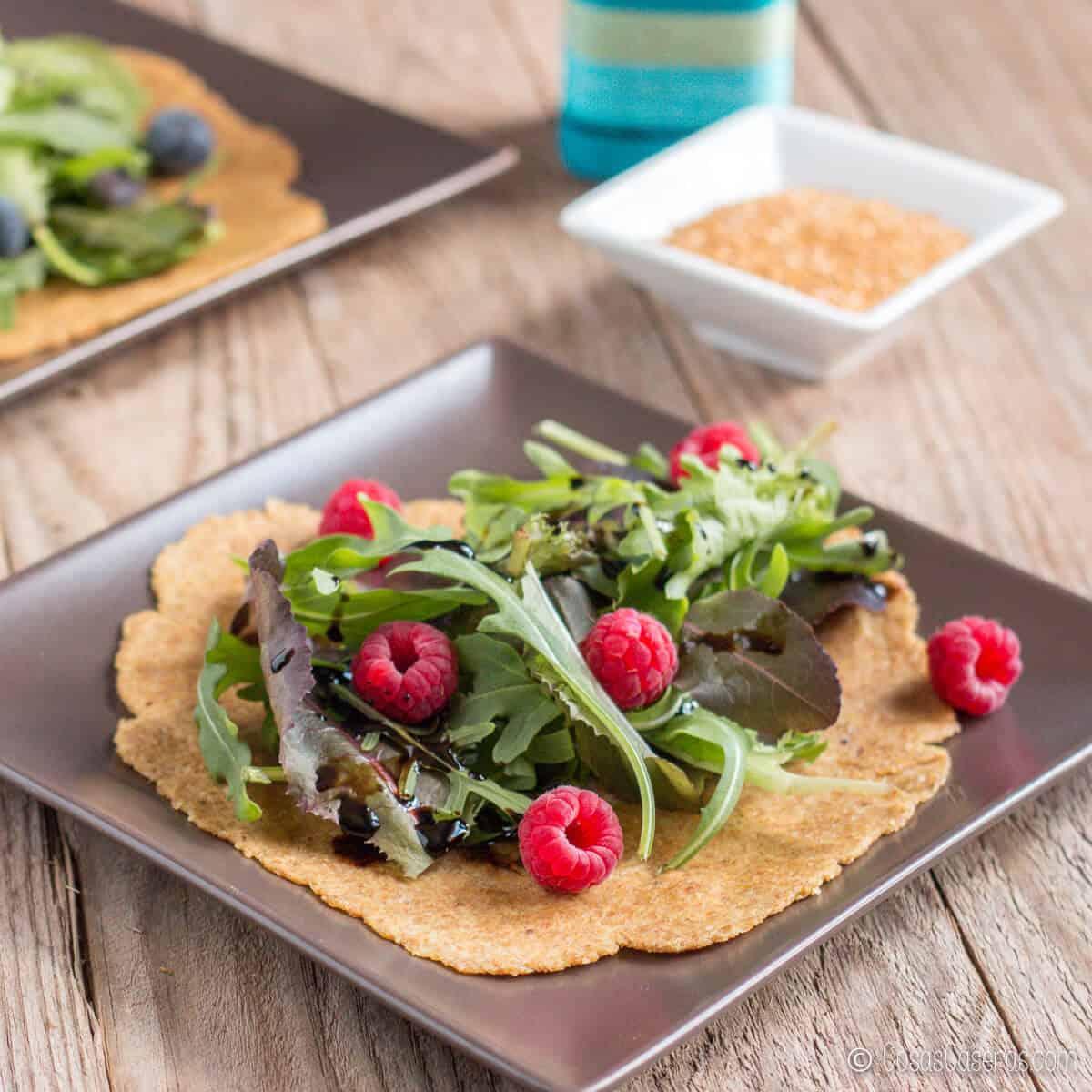 2 tortillas de linaza llenas de lechuga y bayas del bosque (frambuesas y arandanos) al lado de un recipiente con semillas de linaza
