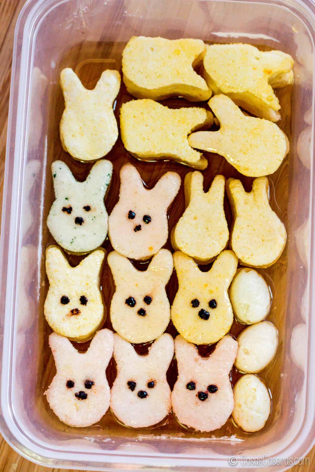 unos masmelos caseros en forma de conejo en una bandeja llena de jarabe de azúcar
