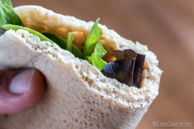 Una ensalada enrollada en un pan pita mostrando su textura