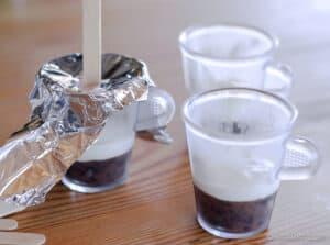 Echando una capa de yogur encima de la capa de puré de arándanos congelada