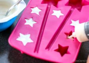 Llenando un molde de silicona de cubitos en forma de estrella con yogur.