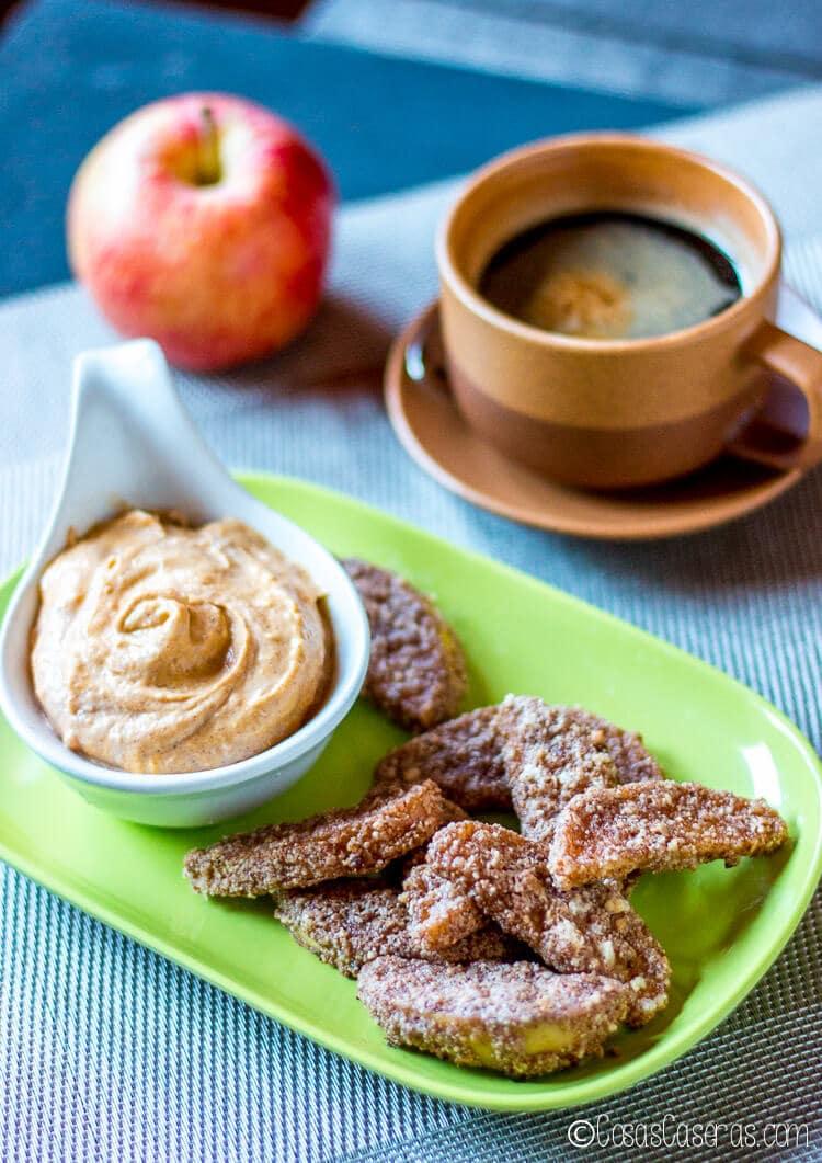 Manzanas fritas en un plato con un cuenco de crema dulce de calabaza para mojar.