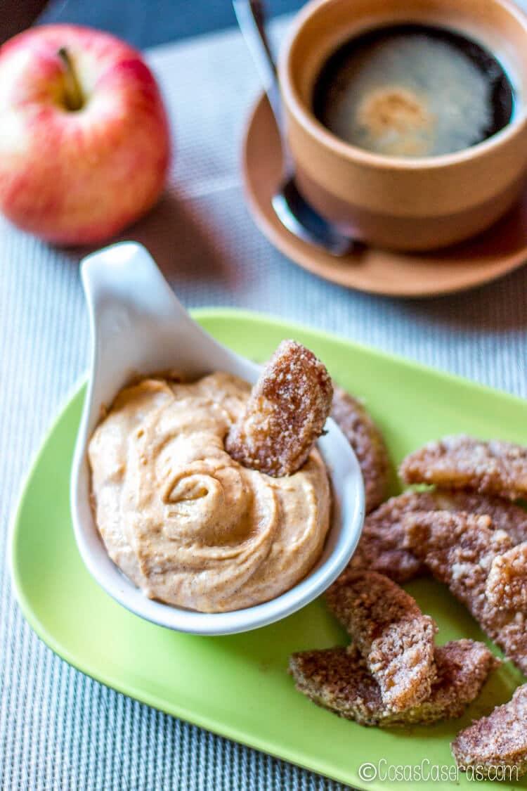 Un plato de manzanas fritas con una sumergida en la crema dulce de calabaza