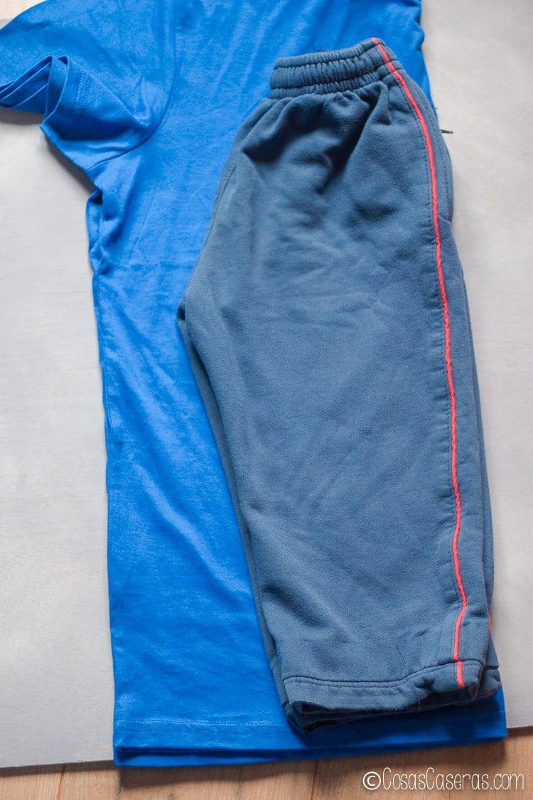 usando un pantalón como patrón para cortar la tela para los pantalones nuevos