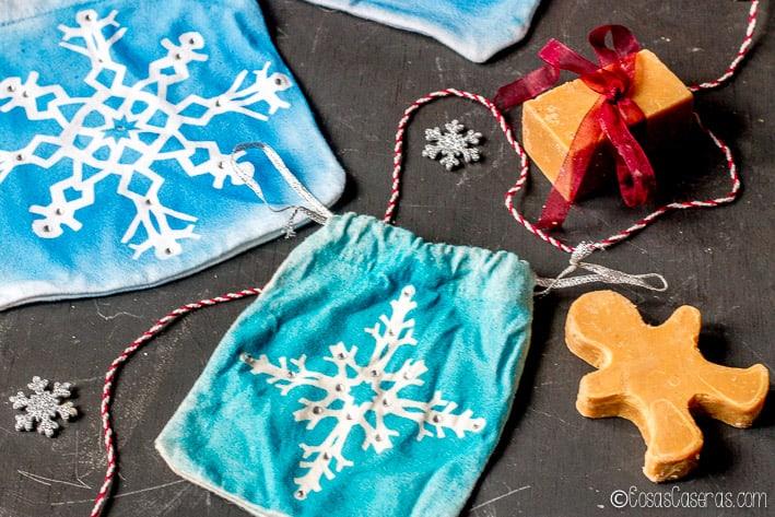 Siempre me ha encantado hacer copos de nieve de papel, pero este proyecto sencillo los convierte en unas preciosas bolsitas de regalo navideñas. Las bolsitas se hacen facilmente de las mangas de camisetas viejas (o puedes usar bolsitas compradas o hechas de otra forma). Estas bolsitas también serían geniales para una fiesta de Frozen. #cosascaseras #bolsas #coser #fiestafrozen #coposdenieve #copitosdenieve #navidad #regalos #envolver #regaloscaseros