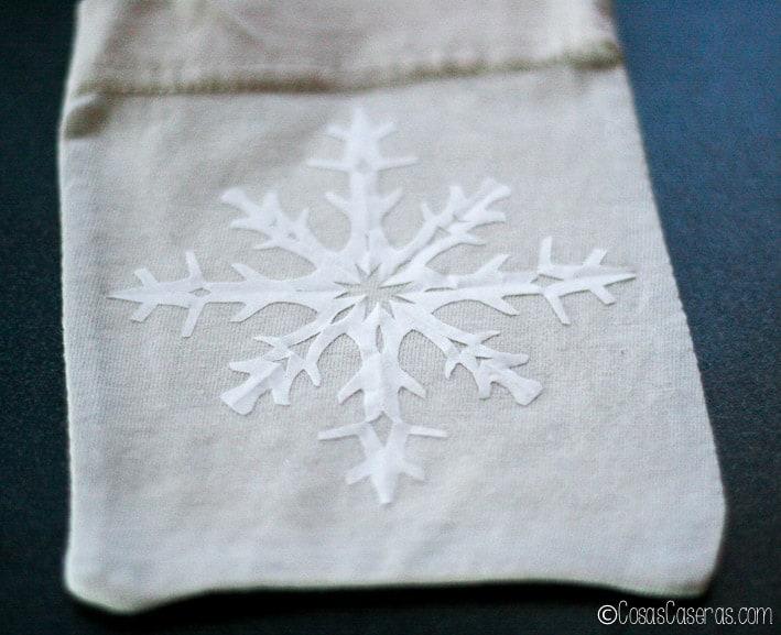 un copo de nieve de papel pegado a una bolsita de tela
