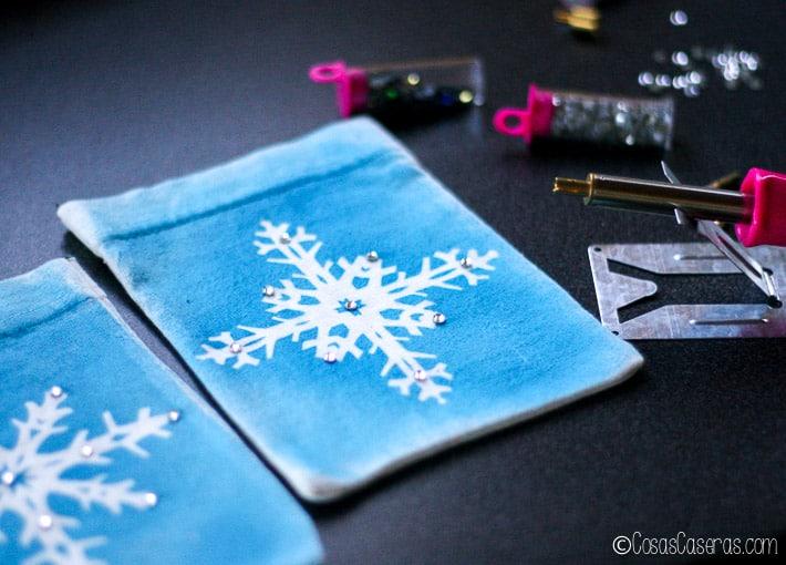 decorando las bolsitas de copos de nieve con unos brillantes