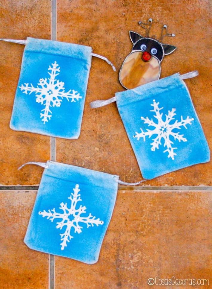 3 bolsitas de regalo con copos de nieve, una con un ornamento navideño hecho de cristas
