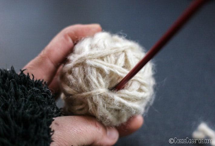 Usando un palo para meter el extremo libre dentro del centro de la lana