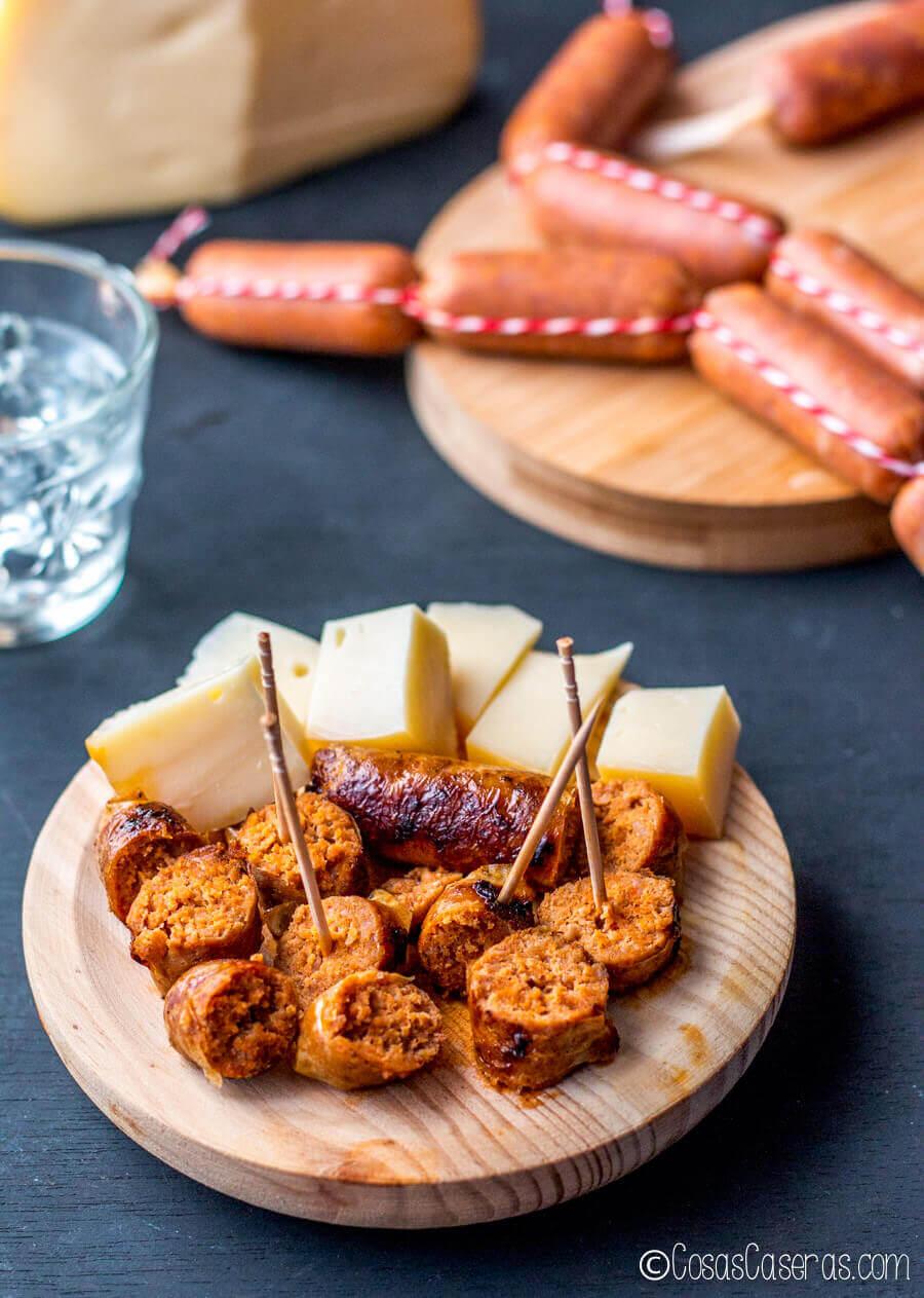 """chorizo casero fresco cocinado y servido con queso. Arriba hay chorizos crudos en una """"tripa"""" de gelatina."""