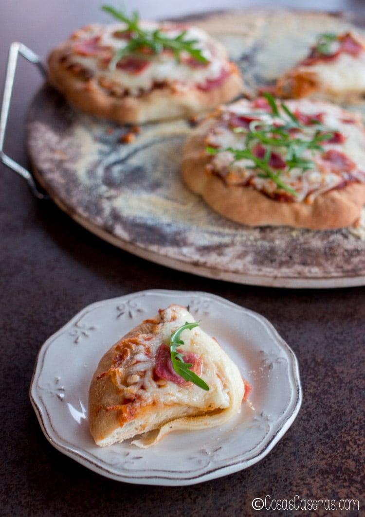 Un trocito de pizza en un plato debajo de una piedra de pizza con varias pizzas de tamaño individual
