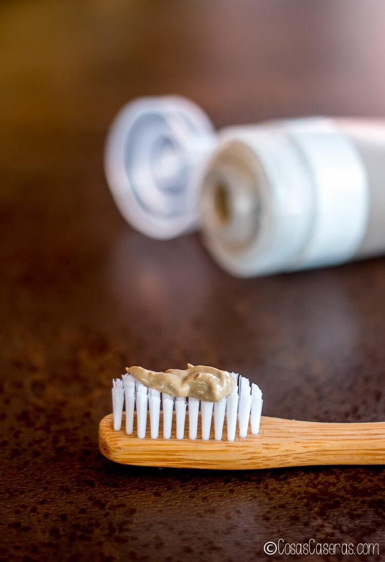 Pasta de dientes natural casera (sin cacao) que se muestra en un cepillo de dientes de bambú