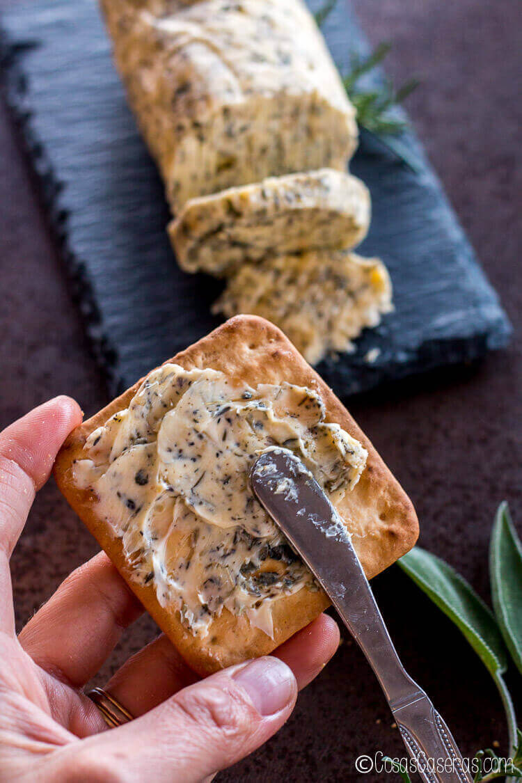 Untando una mantequilla de hierbas sobre una galleta salada.