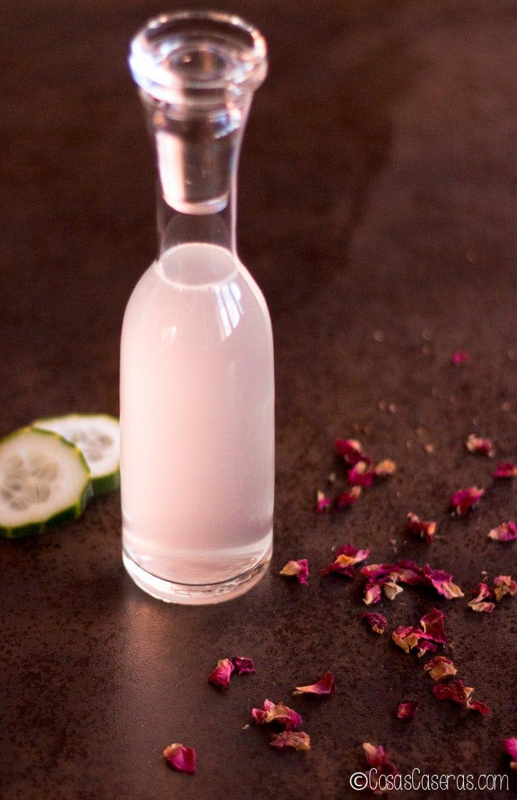 Agua micelar recién hecha con rodajas de pepino y pétalos de rosa.