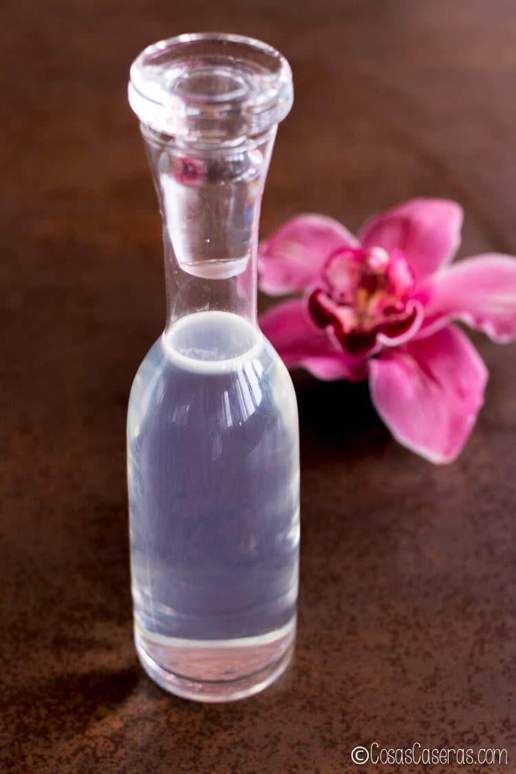 Botella de agua micelar casera delante de una orquídea rosa