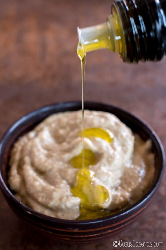 Rociando el baba ganush con aceite de oliva