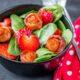 Vista de cerca, una ensalada adornada con rosas de beicon y corazones de fresa