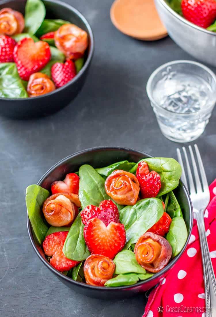 Dos ensaladas adornadas con rosas de beicon y corazones de fresa