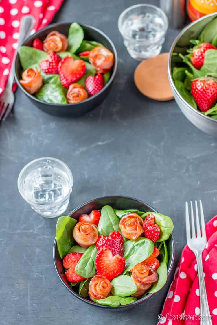 Dos ensaladas adornadas para San Valentín con rosas de beicon y corazones de fresa