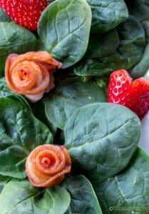 Decorando las espinacas con rosas de beicon y corazones de fresa