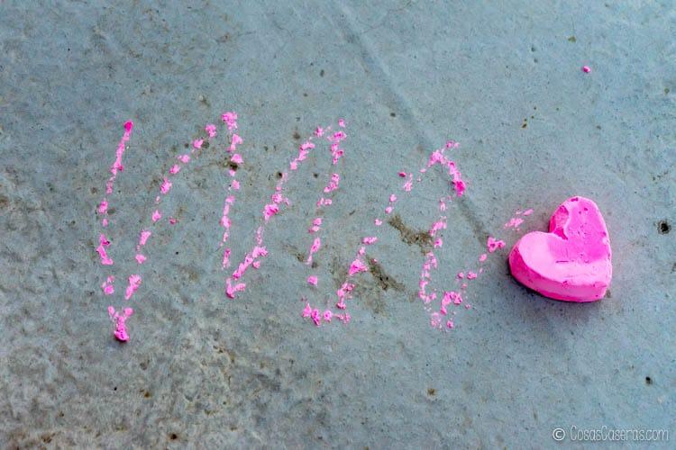 una tiza de color rosa en forma de corazón que se ha usado para escribir en el suelo de hormigón.