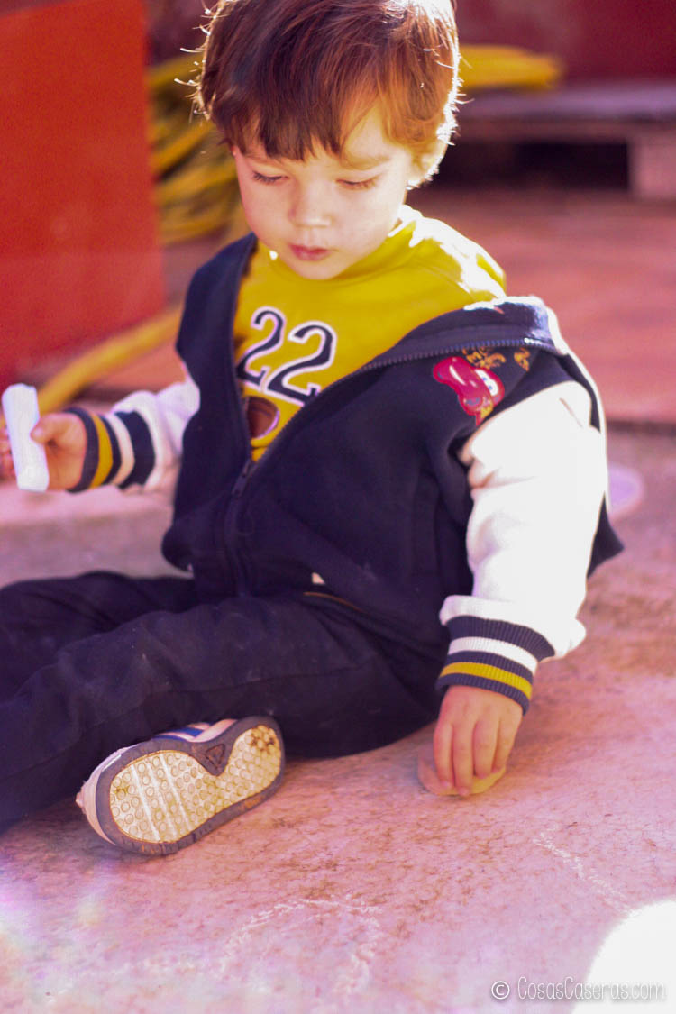Un niño pequeño jugando con tiza casera exterior.