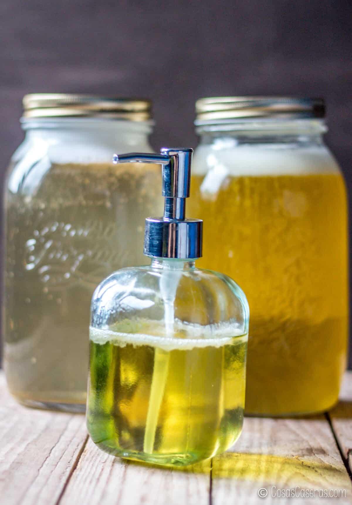 Un jabón líquido delante de dos jarras llenas de jabones líquidos de diferentes colores.