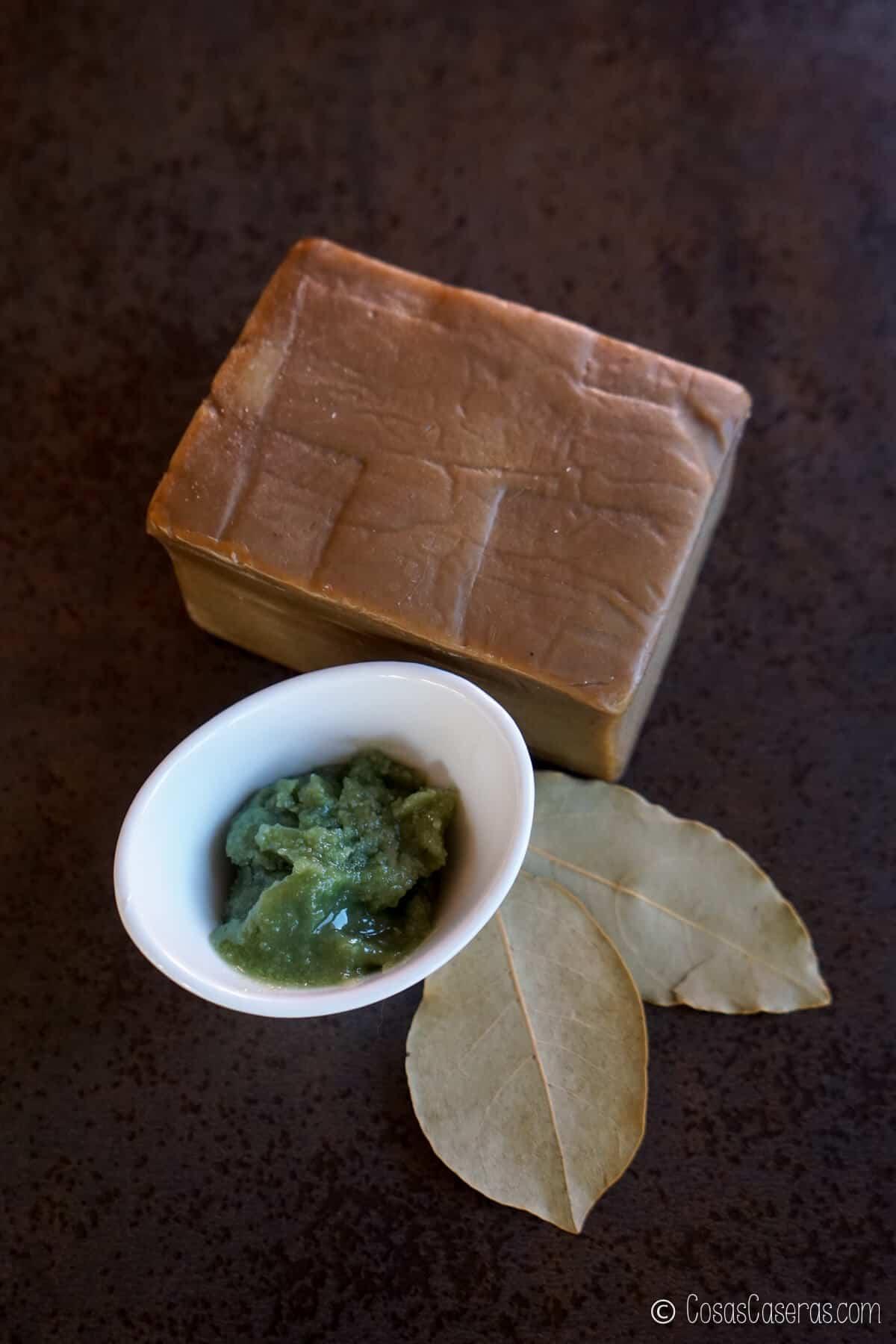 un bol con aceite de bayas de laurel, unas hojas de laurel, y una barra de jabón de Alepo