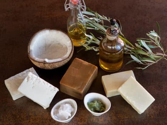 Aceite de coco, aceite de bayas de laurel, aceite de olica y aceite de ricino, al lado de un coco y 2 barras de jabón
