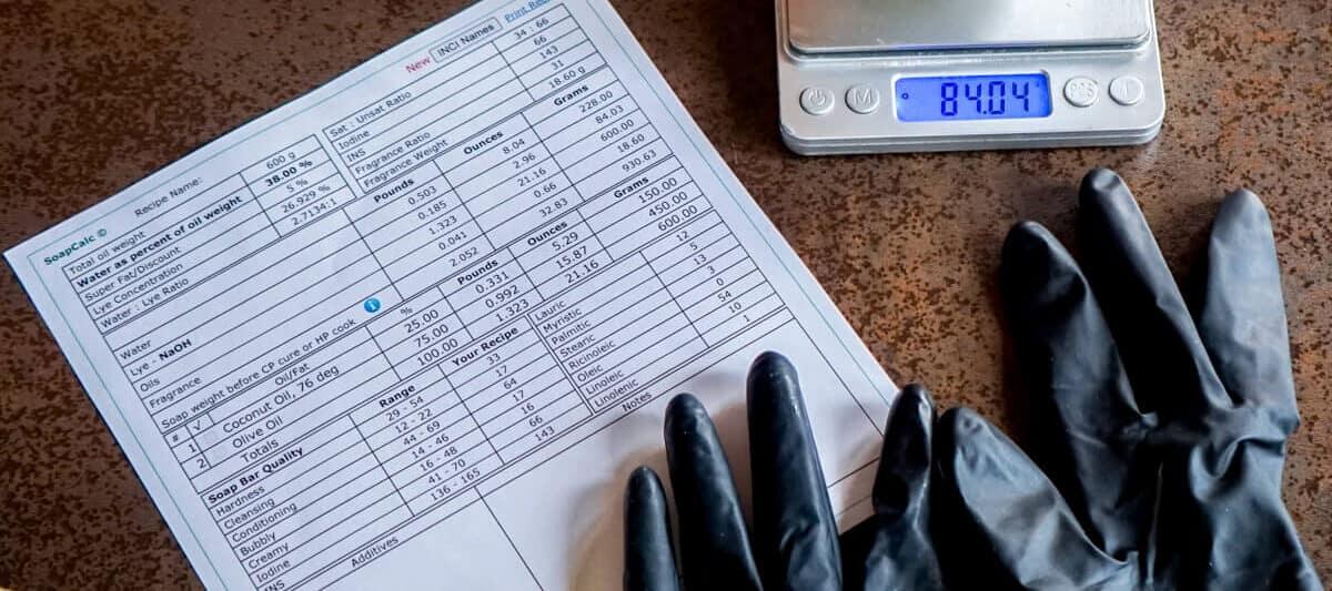 Sosa cáustica en un bol encima de una báscula de cocina, cerca de unos guantes, unas gafas de seguridad y una hoja imprimida de una calculadora de saponificación