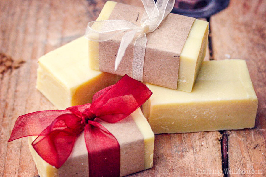 a stack of homemade soaps, two of which have been wrapped in brown paper and ribbons