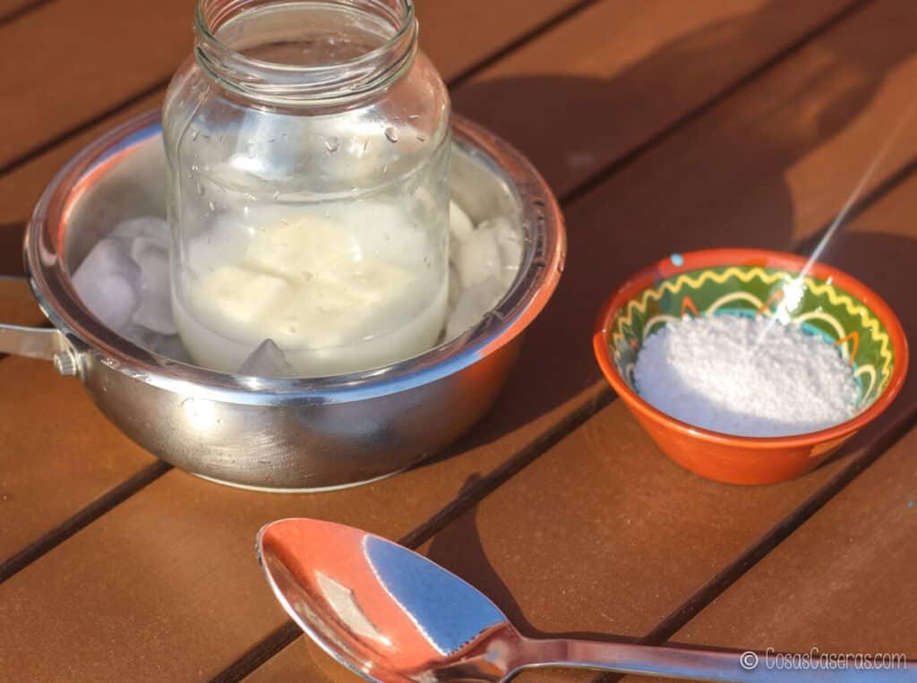 Un bol con sosa cáustica al lado de una cacerola llena de hielo. Dentro, hay un recipiente lleno de agua y leche de cabra congelada.