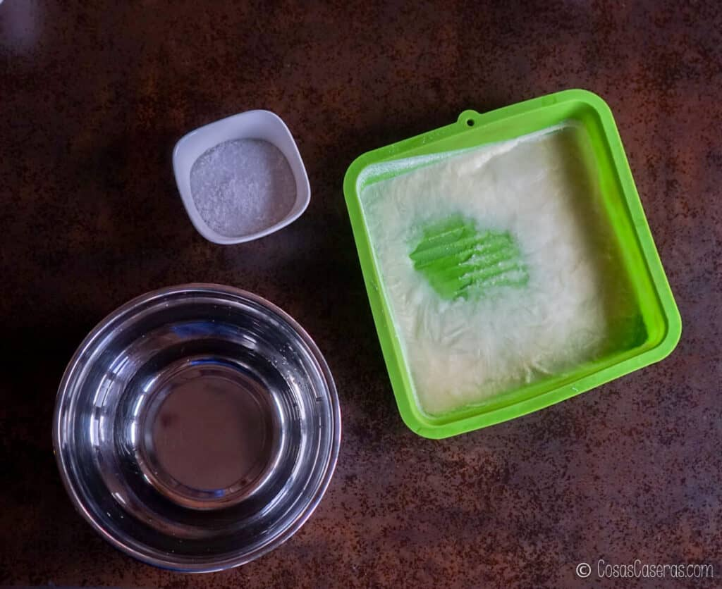 un molde de silicona con leche de cabra congelada, al lado de un bol de agua y otro bol con sosa cáustica