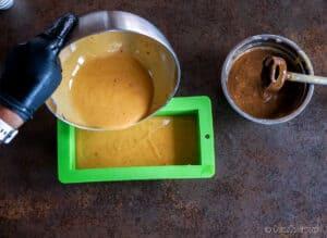 Echando una mezcla de jabón de color dorado en un molde de silicona