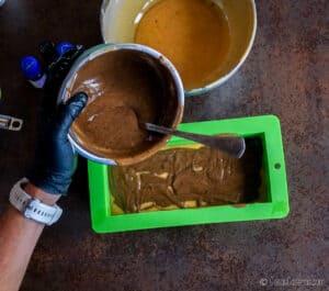 Echando una mezcla de jabón de color marrón sobre uno de color dorado en un molde de silicona