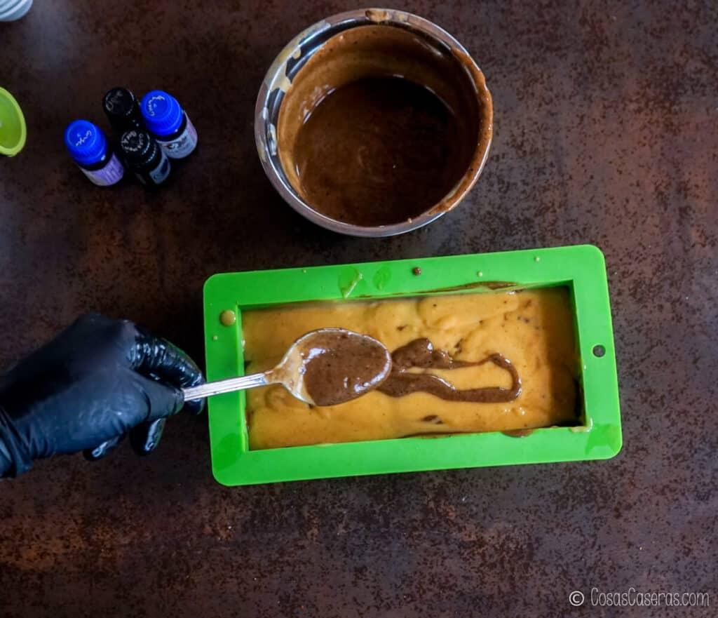 Echando un poco una mezcla de jabón de color marrón sobre uno de color dorado poco a poco con una cuchara.