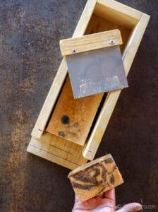 Cortando un bloque de jabón con especias y mostrando una barra de jabón.