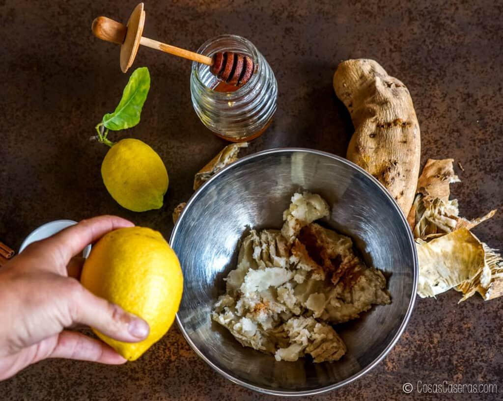 Agregando la ralladura de limón al bol de puré de boniato blanco